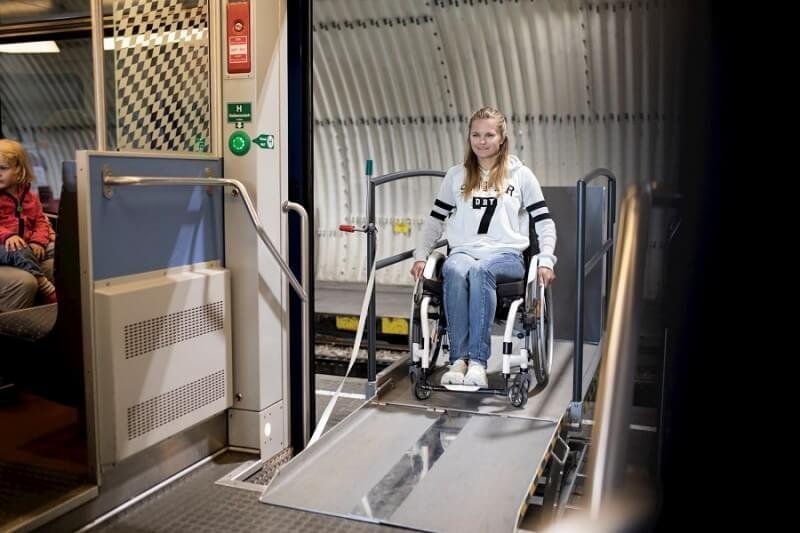 Die Rampe vom Lift wird ausgeklappt und der Rollstuhlfahrer kann die Hebeplattform sicher verlassen.