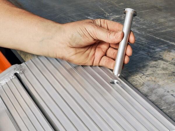 Die Bolzen passen perfekt in die vorgebohrten Löcher im Auflager - damit können Schienen nicht mehr verrutschen.
